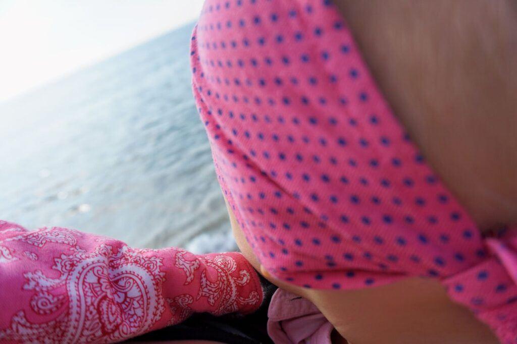 Dítě se kouká z nosítka na moře.