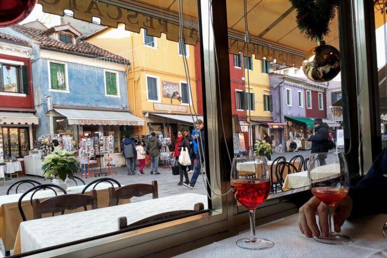 Aperol v restauraci na ostrově Burano s výhledem na ulici.